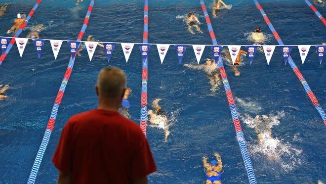 يشاهد المتفرج السباحين وهم يستحمون في IU Natatorium يوم السبت 29 يونيو 2013 خلال اختبارات البطولة الوطنية وبطولات العالم لعام 2013.  كريس بيركين / النجم