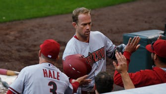 Arizona Diamondbacks manager Chip Hale, left, congratulates Arizona Diamondbacks third baseman Aaron Hill as he returns to the dugout after hitting a three-run home run against the Colorado Rockies in the fourth inning of the first game of a baseball doubleheader Wednesday, May 6, 2015, in Denver.