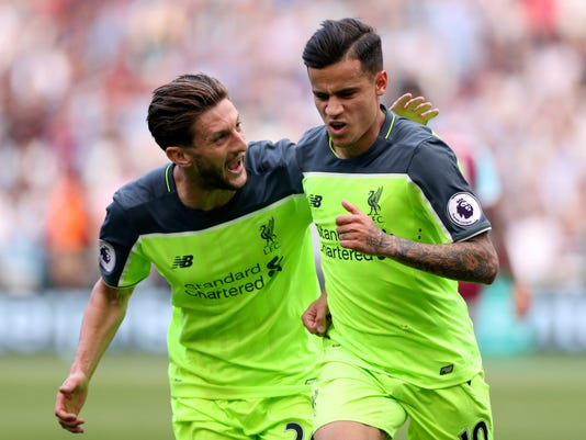 Liverpool's Philippe Coutinho, right, celebrates scoring against West Ham United with teammate Adam Lallana during the English Premier League soccer match at London Stadium, Sunday May 14, 2017. (Adam Davy/PA via AP)