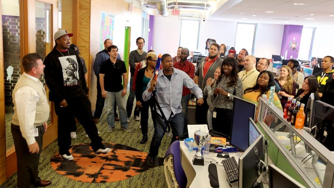 2014 top_workplaces Team members at Quicken Loans gather as Sr. Client Care Specialist Matt Canty, 38, (center) leads the troops on a spontaneous rally to help get any bad energy out so that team members can get back on their phone calls with a refreshed attitude.
