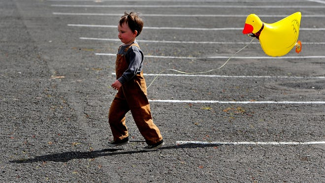 Arlo Brannian, 3, runs with his balloon duck during Oregon Ag Fest at the Oregon State Fairgrounds, on Saturday, April 25, 2015, in Salem.