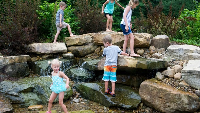 Kids climb on the waterfall feature at the Wesselman's Nature Playscape on Tuesday, June 12. The playscape took four years to develop, design and construct and is the largest in the country.