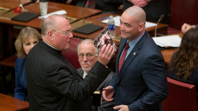 Cardinal Timothy Dolan, left, holds a gift of M&M's presented to him by Sen. Fred Akshar, R-Binghamton, during the opening of the legislative session Wednesday in the Senate Chamber at the Capitol in Albany.