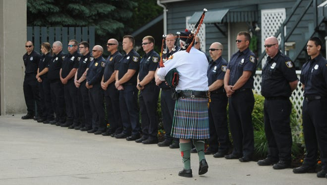 Jim Nichols walks past a line of Richmond firefighters during Friday's memorial service.