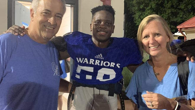 Samson Stearns, center, hugs his adopted parents Dave and Shelley Stearns after an Oconee County High School football game.