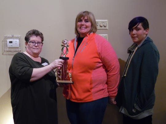 Ann Bennett, left, Executive Director of Neighbor to Neighbor Volunteer Caregivers of Door County, presents the first-place trophy from the Neighbor to Neighbor Rib Fest to Trisha Prahl and Isaac of the Casey's BBQ & Smokehouse team.