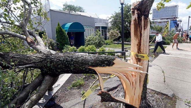 People survey damage in front of a funeral home in Revere, Mass., Monday, July 28, 2014, after a tornado touched down.