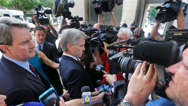 Former Virginia Gov. Bob McDonnell, center, tries to move through the throng of media as he and his lawyer, John Brownlee,  left, arrive Aug. 19, 2014, at federal court in Richmond, Va.