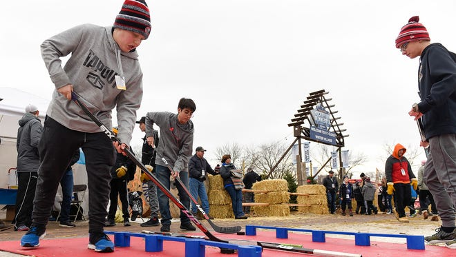 Fans play games in the winter village Saturday, Jan. 20, during Hockey Day Minnesota at Lake George.