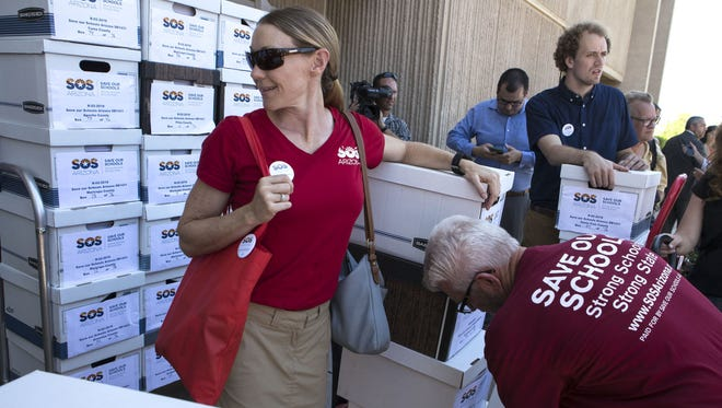 Karen Gresham of the Save Our Schools Arizona campaign is surrounded by boxes of signatures on Tuesday, Aug. 8, 2017, at the State Capitol in Phoenix. The group delivered 111,540 signatures and Gov. Doug Ducey was notified Friday, Sept. 8, 2017, that foes of his school-voucher expansion law had qualified their referendum for the November 2018 ballot