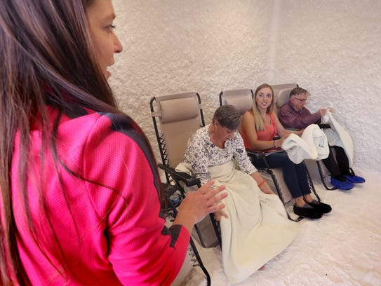 The Salt Room owner Tammra Reiss readies Kathy Tarmann (left), reporter Jordyn Noennig and Bill Laesch in zero-gravity reclining chairs in one of two salt therapy rooms. The room's walls and floor are covered in salt, and salt vapors are circulated through the room during a 45-minute treatment.