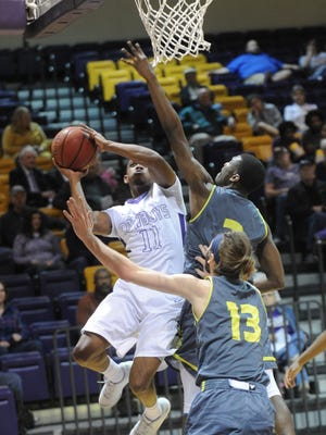 HSU's Christian O'Neal (11) drives to the basket while Howard Payne's J Bailey (13) and a teammate defend. HSU won the American Southwest Conference West Division game 100-85 on Thursday, Jan. 12, 2017 at the Mabee Complex.