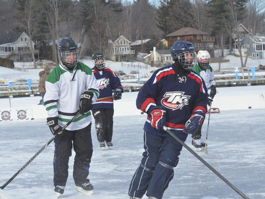 Hockey players play on Malletts Bay during the Pond