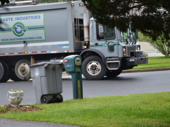 A waste industries truck moves around a neighborhood