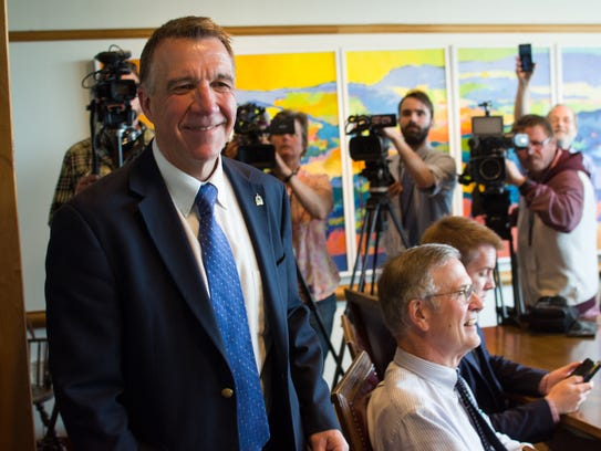 Gov. Phil Scott smiles as he enters a news conference