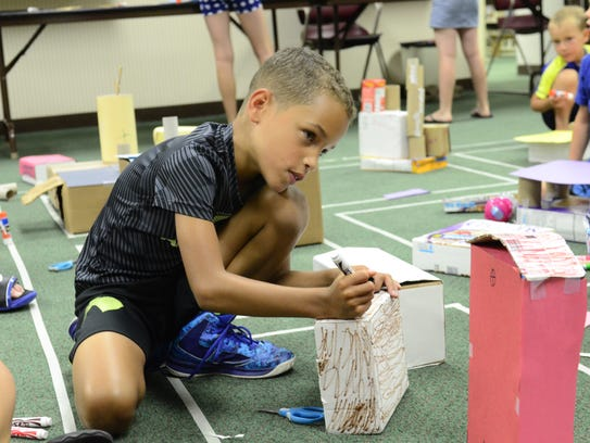 Evan Butler, 7, of Fremont makes a barn and house with
