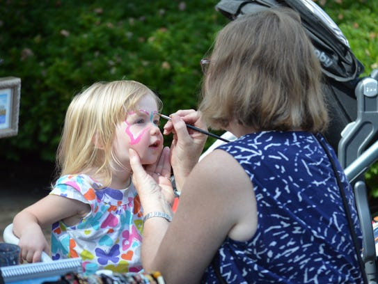 Catherine Jacob, 2, of McLean, Va., gets her face painted