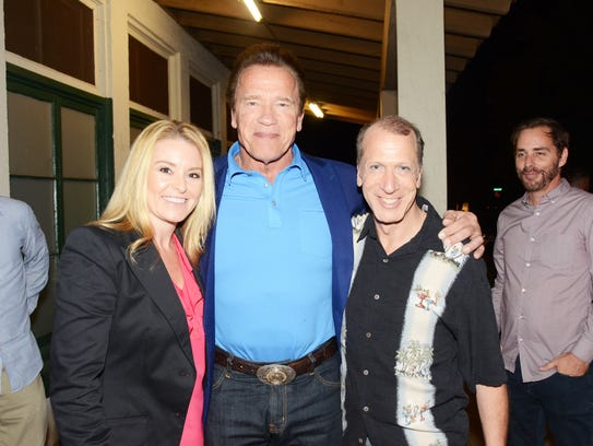 Arnold Schwarzenegger in the middle with his girlfriend