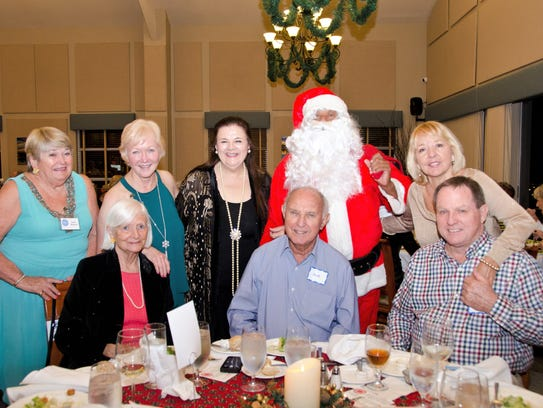 Santa poses with guests at the World Wings annual December