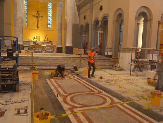 Workers stay busy inside Sacred Heart Cathedral.