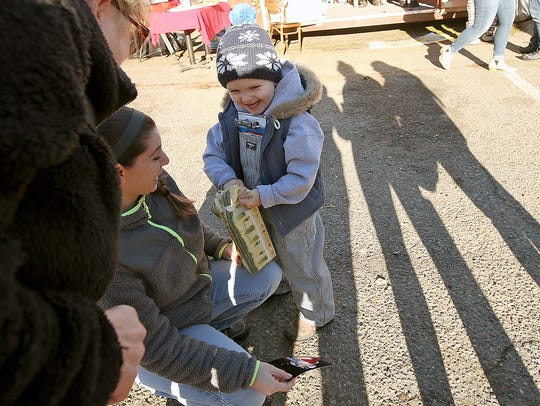 Gabriel Benson, 3, is all smiles as his mother, Kayla Hornbeck, helps him open the brand new toy firetruck he received at the Camp Union Saloon.