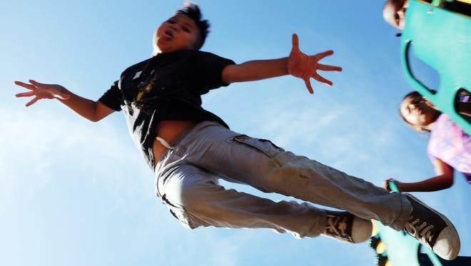 Jaime Castro, 10, leaps off the play structure behind the Hebbron Family Center in Salinas.