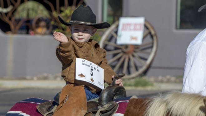 A participant waves in the Wild West Days Parade in Cave Creek on Saturday, Nov. 7, 2015. The parade was part of a three day event, celebrating Arizona's western culture.