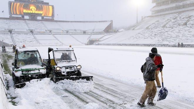 Workers clear snow off Kinnick Stadium's field before  Iowa-Purdue.