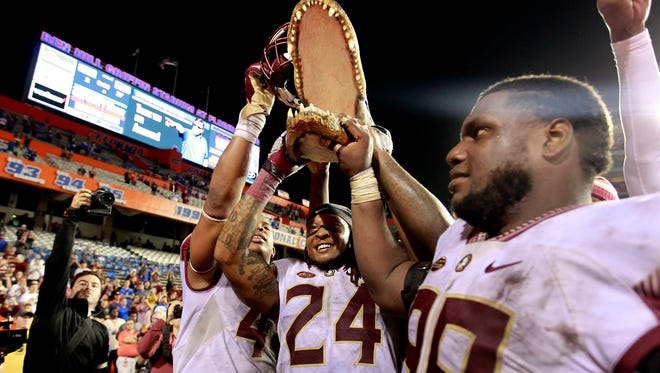 Seniors Nile Lawrence-Stample and Terrance Smith hold up the Gator head in celebration after FSU's 27-2 win over Florida.