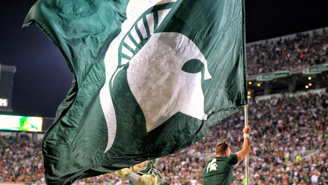 Michigan State Spartans flag after a score against the Jacksonville State Gamecocks during the second half of a game at Spartan Stadium. MSU won 45-7.