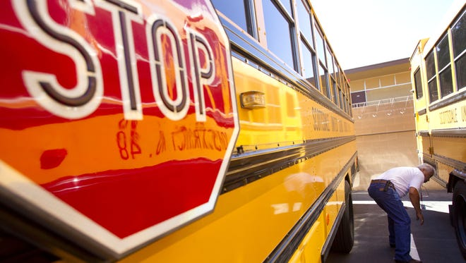 A bus driver for Scottsdale Unified School District inspects his bus after his morning route.