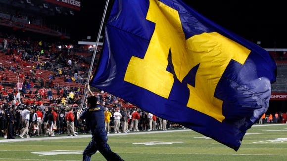 A Michigan flag bearer celebrates a touchdown during