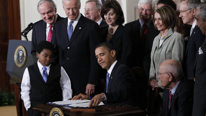 In this March 23, 2010, file photo, President Barack Obama reaches for a pen to sign the Affordable Care Act, also known as Obamacare, in the East Room of the White House in Washington.
