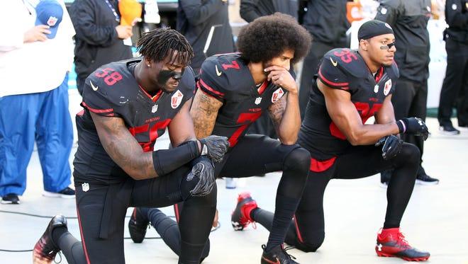 San Francisco 49ers quarterback Colin Kaepernick, center, knelt for the national anthem last season.