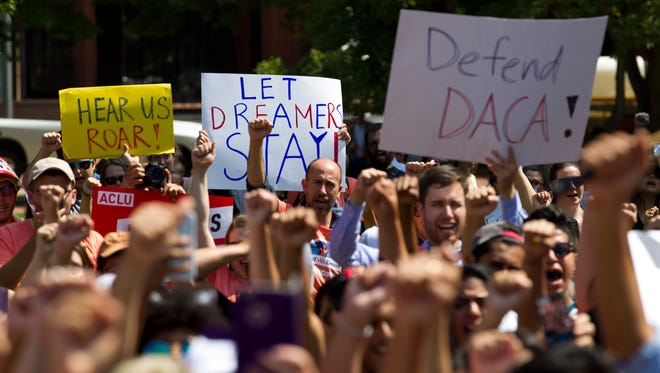 Protesters hold up signs during a rally supporting Deferred Action for Childhood Arrivals, or DACA, outside of the White House in Washington, on Tuesday, Sept. 5, 2017.