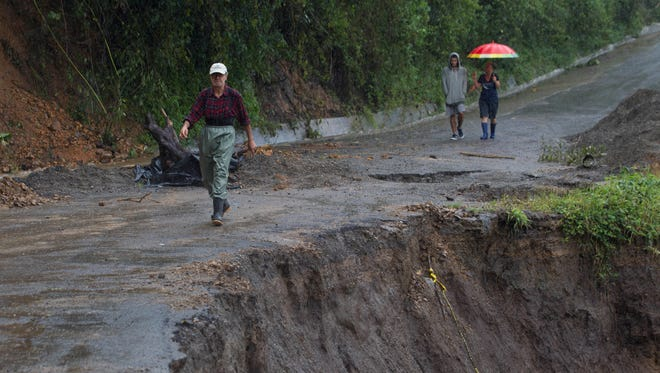 Neighbors walk under the rain past a washed out road in Alajuelita on the outskirts of San Jose, Costa Rica, Thursday, Oct. 5, 2017. Tropical Storm Nate formed off the coast of Nicaragua on Thursday and was being blamed for at least 17 deaths in Central America as it spun north toward a potential landfall on the U.S. Gulf Coast as a hurricane over the weekend.
