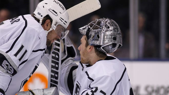 Los Angeles Kings forward Anze Kopitar (11) talks to goaltender Jonathan Quick (32) during a break in the action against the Toronto Maple Leafs at the Air Canada Centre.