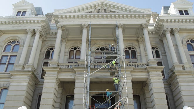 Construction workers remove scaffolding Nov. 28, 2017, from the exterior of the Tippecanoe County Courthouse.