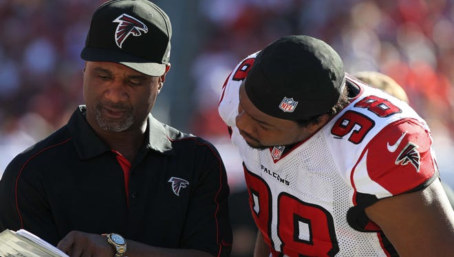 November 25, 2012; Tampa, FL, USA; Atlanta Falcons special teams coordinator Keith Armstrong talks with defensive end Cliff Matthews (98) during the second half against the Tampa Bay Buccaneers at Raymond James Stadium. Atlanta Falcons defeated the Tampa Bay Buccaneers 24-23.