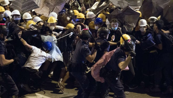 Police use batons against pro-democracy protesters near the government headquarters in the Admiralty district of Hong Kong on Dec. 1, 2014.