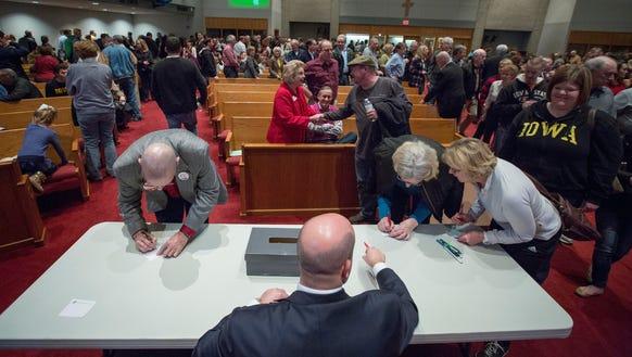 Caucusgoers cast their ballots at Gloria Dei Lutheran