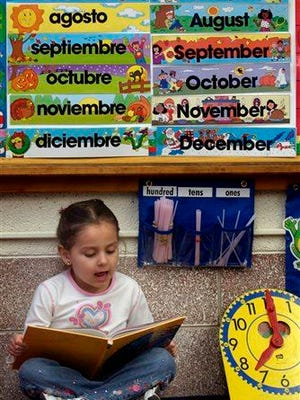 Kasandra Herrera, 6, reads a book in Spanish in Bianca Alvarez's dual language first grade classroom at Northwest Elementary School in Dodge City, Kan.