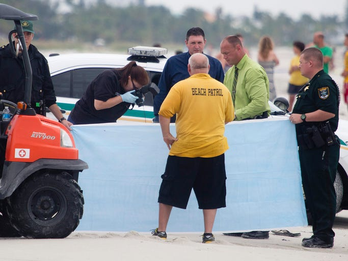 Members of the Lee County Sheriff's Office investigate the scene of a lightning strike on Fort Myers Beach on Tuesday 7/22/2014.  One person was killed and two people were injured in the strike.
