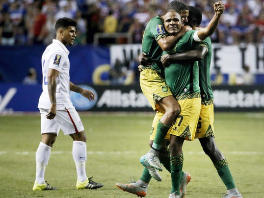 Jamaica's Rudolph Austin, facing camera, celebrates with teammates Joel McAnuff, left, and Je-Vaughn Watson, right, as United States' DeAndre Yedlin walks off the pitch after Jamaica defeated the United States 2-1 in a CONCACAF Gold Cup soccer semifinal on Wednesday in Atlanta.