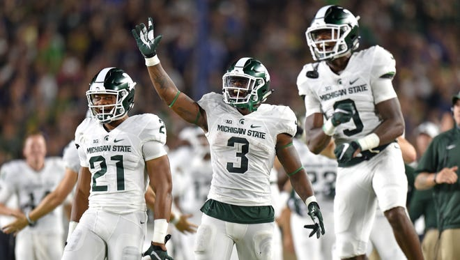 Spartans Cam Chambers (21), LJ Scott (3) and Donnie Corley (9) celebrate Gerald Holmes's second touchdown of the night.