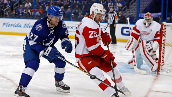 Jonathan Drouin of the Tampa Bay Lightning forechecks against Mike Green of the Detroit Red Wings during the second period at the Amalie Arena on Oct. 13, 2016 in Tampa.