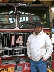 Southport volunteer firefighter Chris Baldwin stands in front of a New York Fire Department truck during a trip to New York City for cancer treatment.