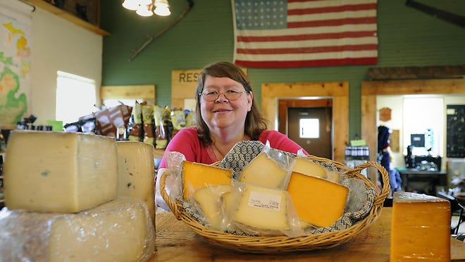 Janice Williams shows some of the Tirrell family's homemade cheeses at the Tirrell Farmstead Specialties store in Charlotte Thursday. The store features Michigan and locally-made food and other items. Several will be featured during Eaton Food and Ag Fest at the Eaton County Fair on Monday.