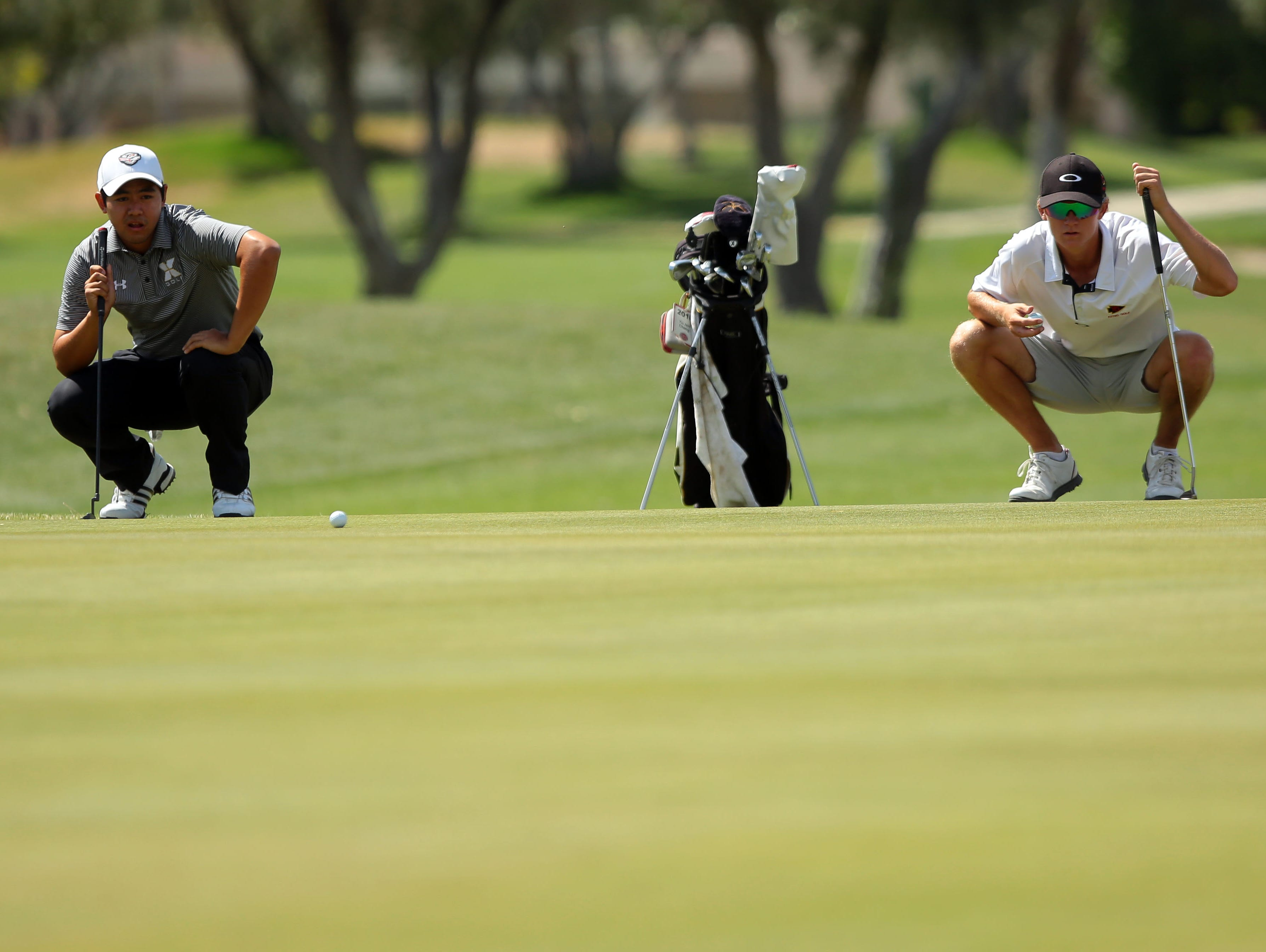 Xavier's Shawn Tsai (left) and Palm Desert's Jake Vincent (right) simultaneously read the ninth green during the Desert Valley League boys golf individual championship tournament Thursday, April 28, 2016, on the North Course at Indian Canyons Golf Resort in Palm Springs, Calif.