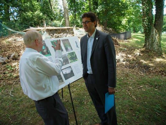 """Rockwood Park & Museum director Philip Nord shows New Castle County Executive Matt Meyer a poster outlining the history of the """"gas house."""""""